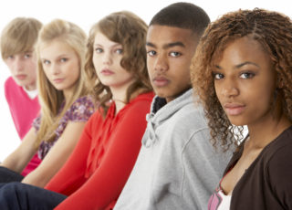 Studio Portrait Of Five Teenage Friends In Line looking serious