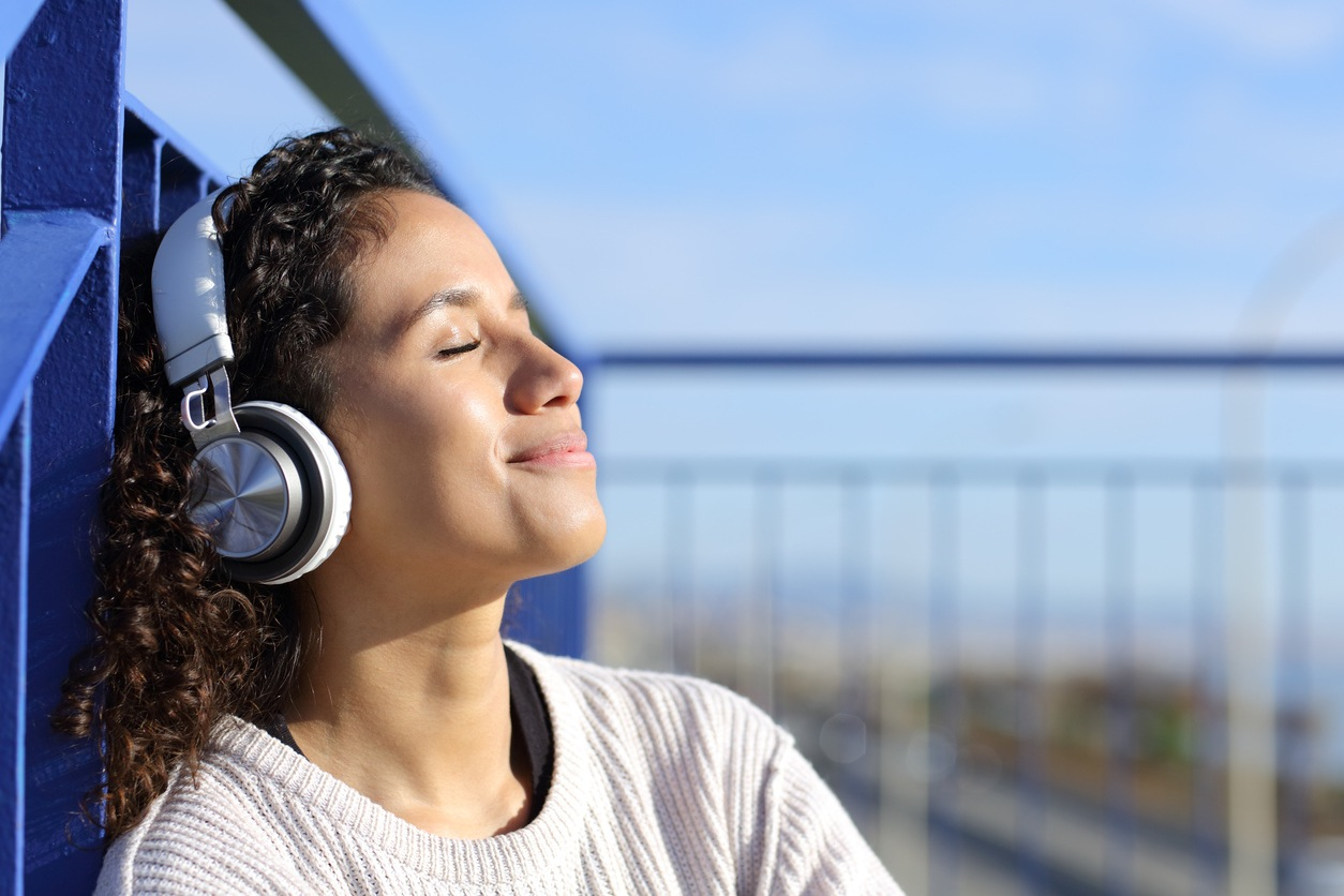 Relaxed latinx girl listening to music outdoors