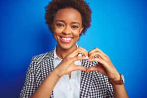 African american business executive woman over isolated blue background smiling in love showing heart symbol and shape with hands. Romantic concept.