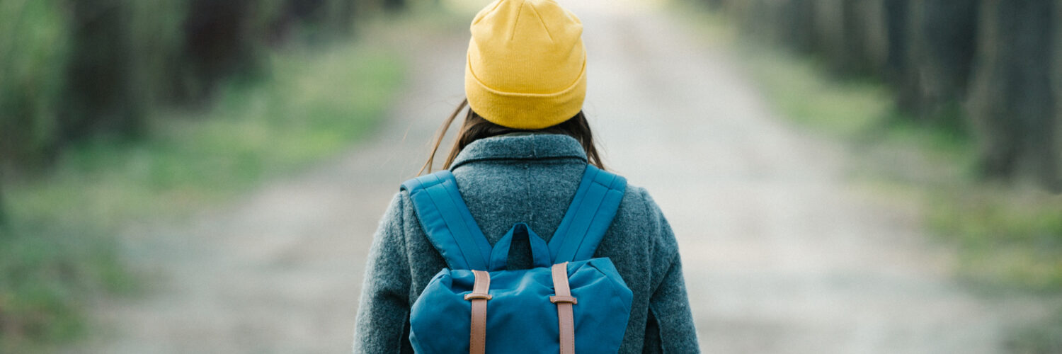 Young woman walking on an avenue on her travel journey. Travel and fashion concept.