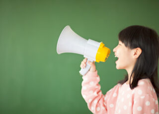 happy kid using a megaphone to shout with blackboard