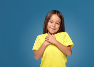 little girl in yellow t-shirt hands on her heart on the blue background